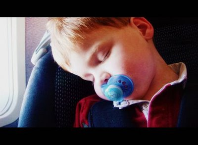 Child sleeps in car seat on plane