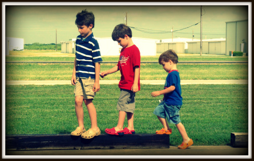 Three boys walking on a railroad tie