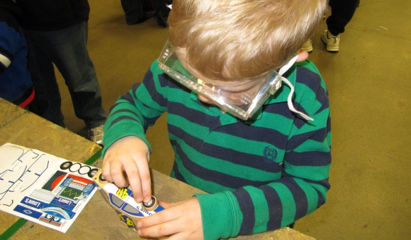 Boy putting stickers on wooden car