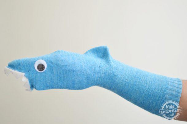 A man wearing Shark sock puppet is shown