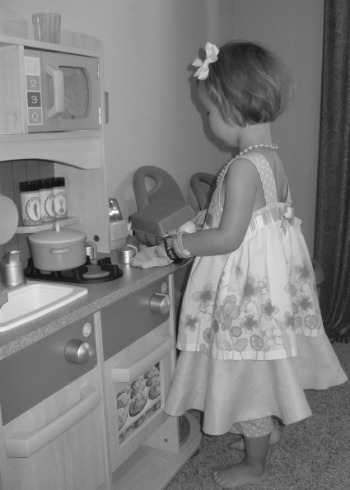 little girl in pretend kitchen