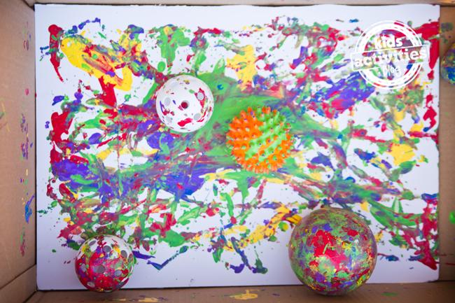 Projet de peinture avec des boules pour les tout-petits et les enfants d'âge préscolaire - toile au fond de la boîte en carton avec des boules remplies de peinture et des traînées de couleur.