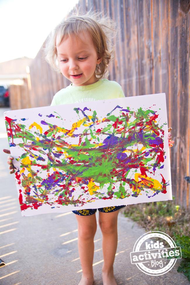 Peinture avec des balles - enfant tenant une toile d'art de balle avec des couleurs vives d'orange, rouge, vert, jaune et rouge