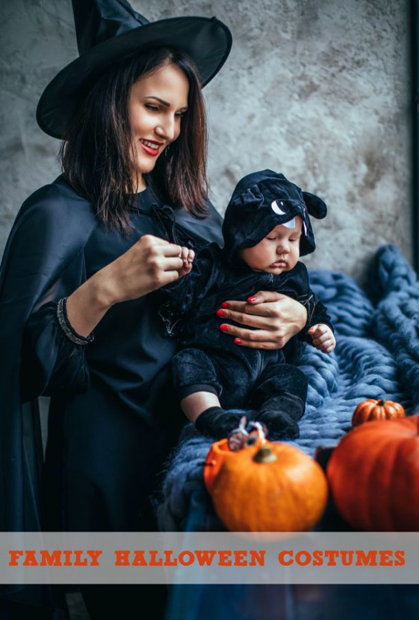 A mom and her son dressed up in black Halloween costumes.