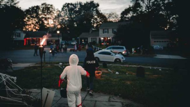 Kids dressed up in Halloween costumes and trick-r-treating in a suburban neighborhood.