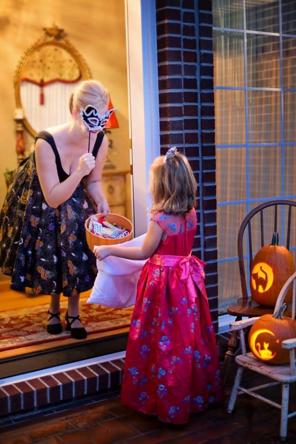A young girl in a pink princess dress trick-r-treats at her neighbor's house.