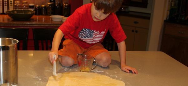 boy paints butter on cinnamon roll dough