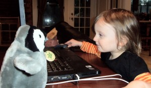 baby and penguin at computer