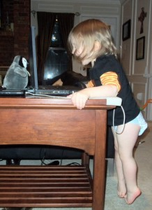 child on tip toes at computer