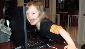 child at computer screen laughing