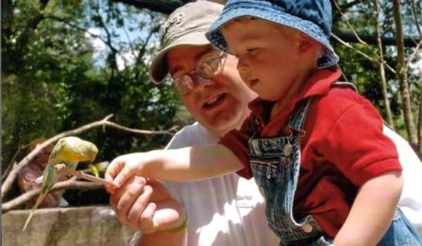 dad and boy feeding bird at ft worth zoo