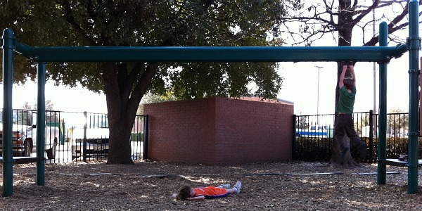 boy lays under play equipment at the park