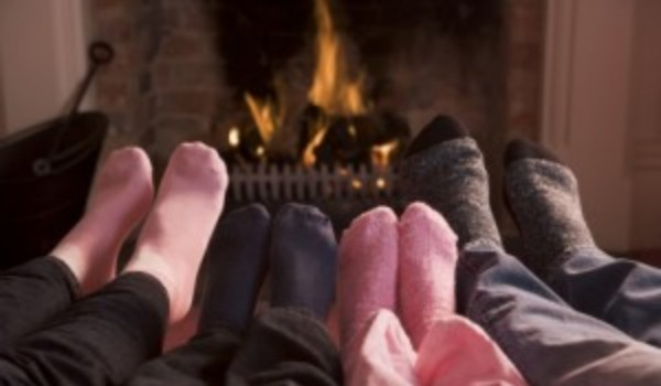 family feet in front of fireplace