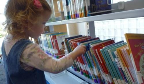 little girl at library book shelf 600x350