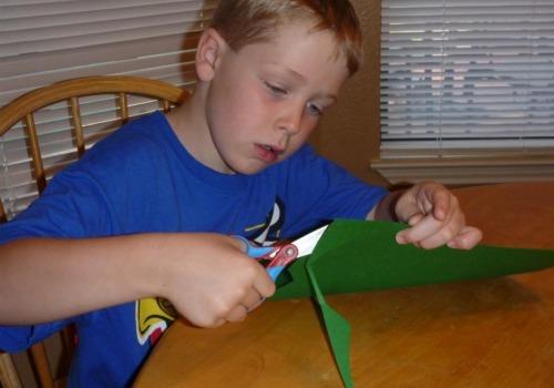boy cutting green paper
