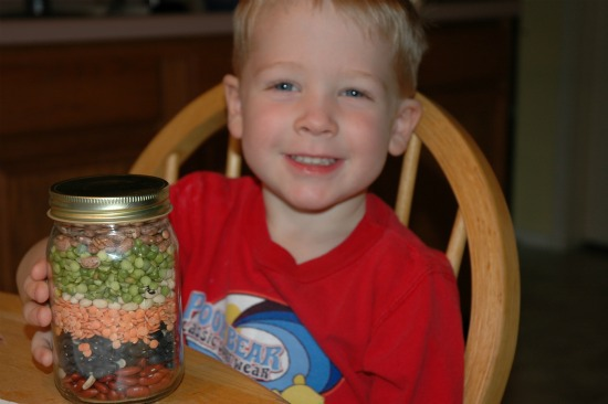 little boy with jar of layered beans