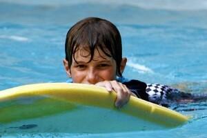 boy swimming in pool with kickboard