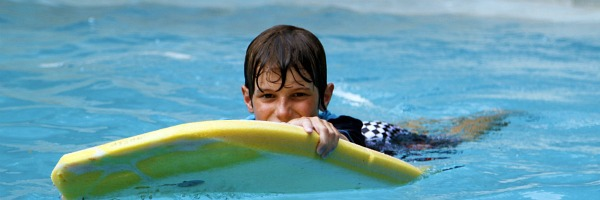 boy swimming in pool with kickboard