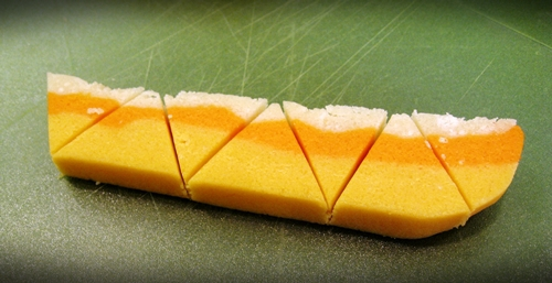 Candy corn sugar cookie dough that is cut into triangles and yellow, orange, and white