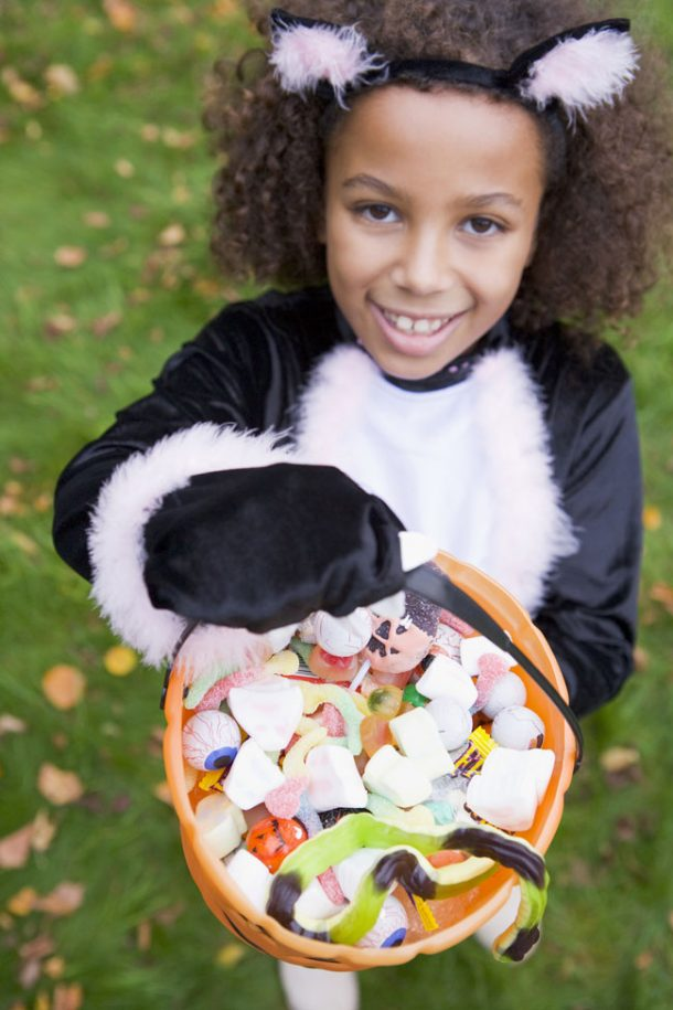 A girl dressed in a Halloween costume is holding up a bucket filled to the brim with candy and toys.