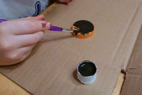 child painting bottle cap