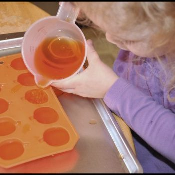 girl pouring into pumpkin ice cube tray