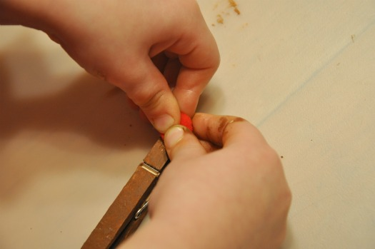 child gluing red ball on clothespin