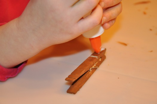 child putting glue on clothespin