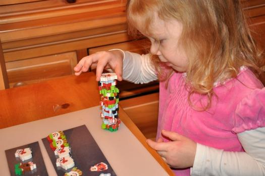 little girl stacking Christmas erasers
