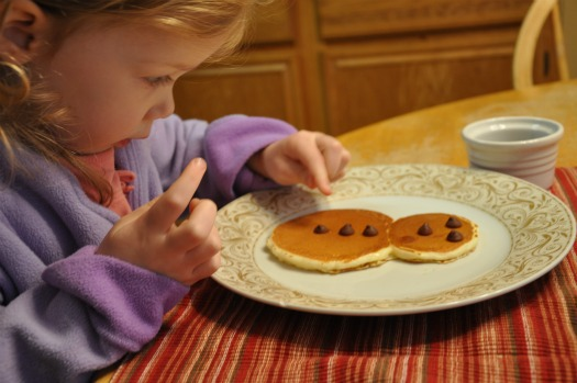 little girl with chocolate chip pancakes