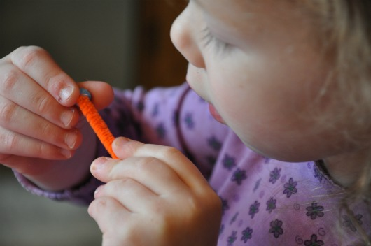 girl with orange pipe cleaner and blue bead