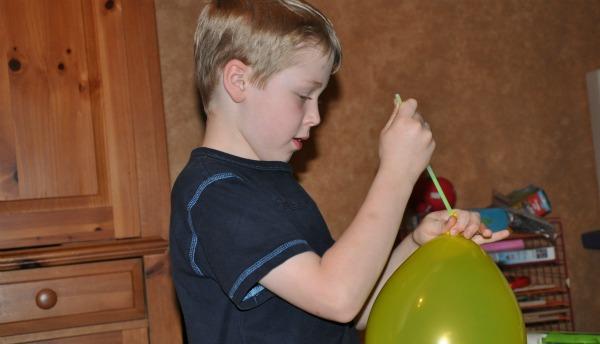 boy putting glow stick in balloon