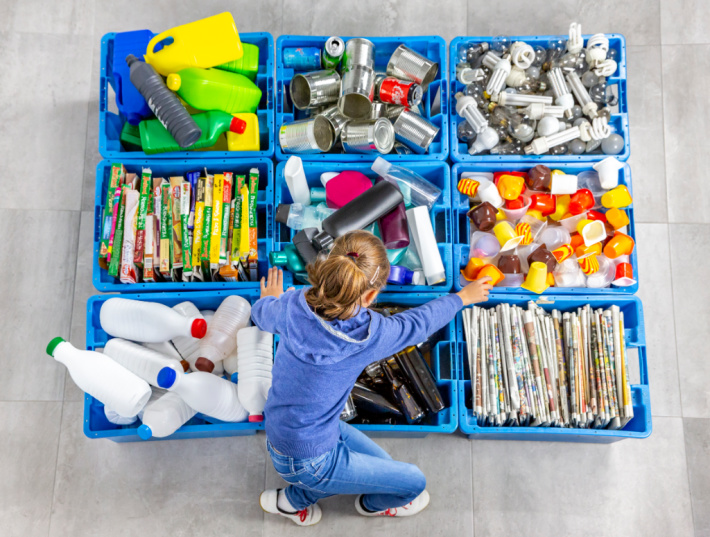 Recycling center with girl sorting recyclables - Kids Activities Blog
