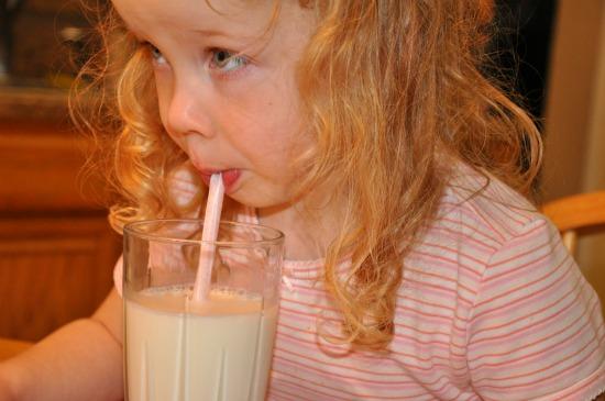 girl drinking milk with straw
