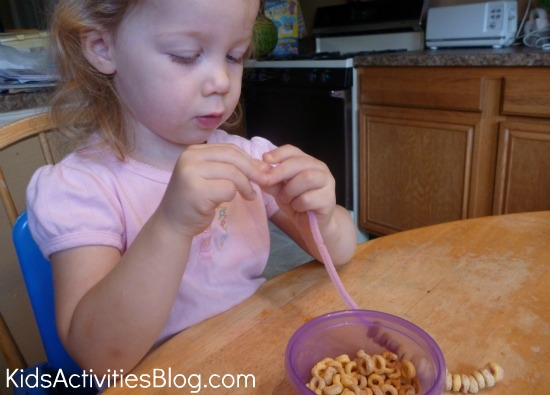 girl stringing cheerios on pipe cleaner