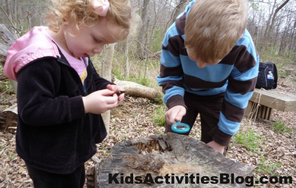 kids exploring in woods on Earth Day April 22 - two kids looking at a stump with magnifying glass