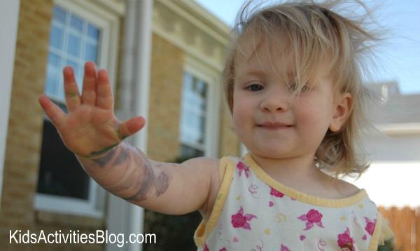 petite-fille-avec-peinture-sur-main-et-bras