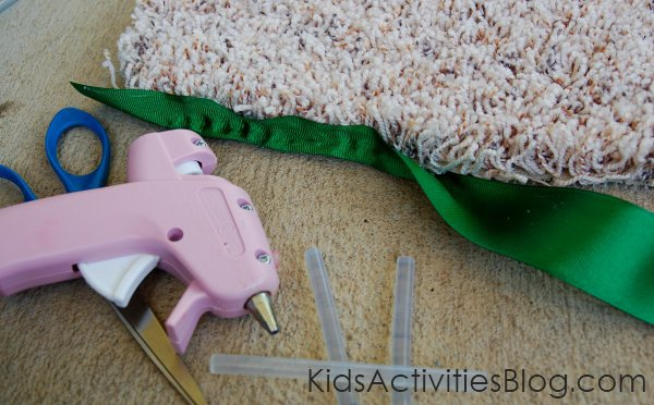 binding the rug - carpet remnant - with a glue gun and green ribbon