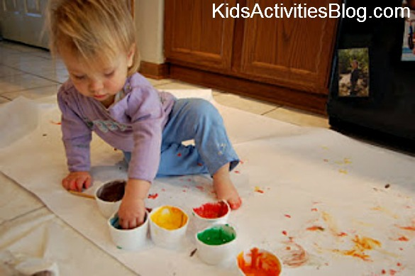 girl fingerpainting on floor