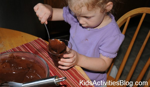 little girl making chocolate pudding