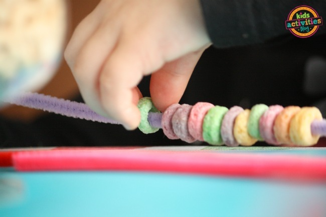 threading cereal on a pipe cleaner
