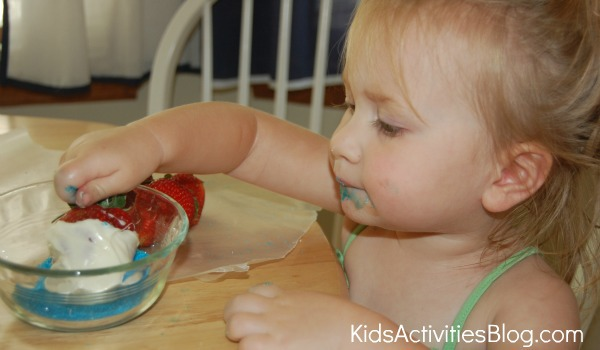 little girl dipping strawberries