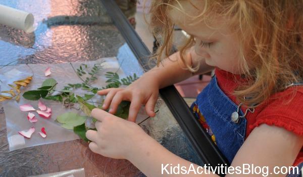 petite fille faisant un collage de nature