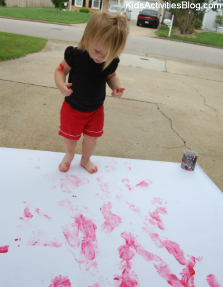 little girl painting red feet