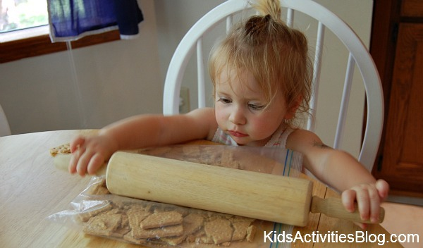 little girl rolling graham crackers