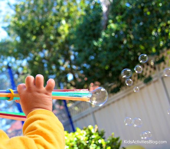petit enfant utilisant une baguette de tir à bulles pour souffler des bulles à travers la clôture de l'arrière-cour
