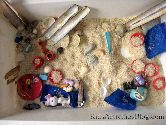 The seaside ocean sensory bin made at home with rice, toys, shells and more