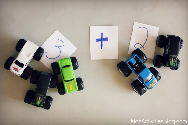 monster trucks math with numbers written on cards and plus sign.