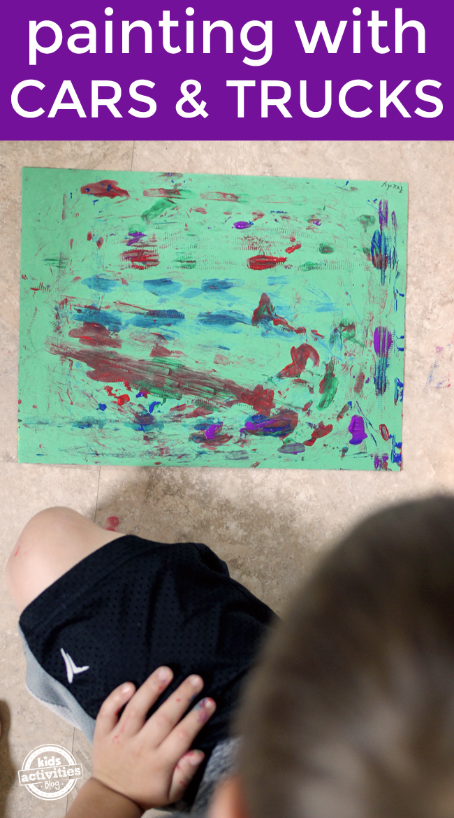 Painting with Monster Trucks preschool art activity for kids - finished art project shown with child