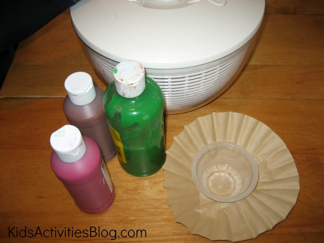 Thanksgiving art supplies: a cupcake liner, salad spinner, green paint, red paint, and brown paint.